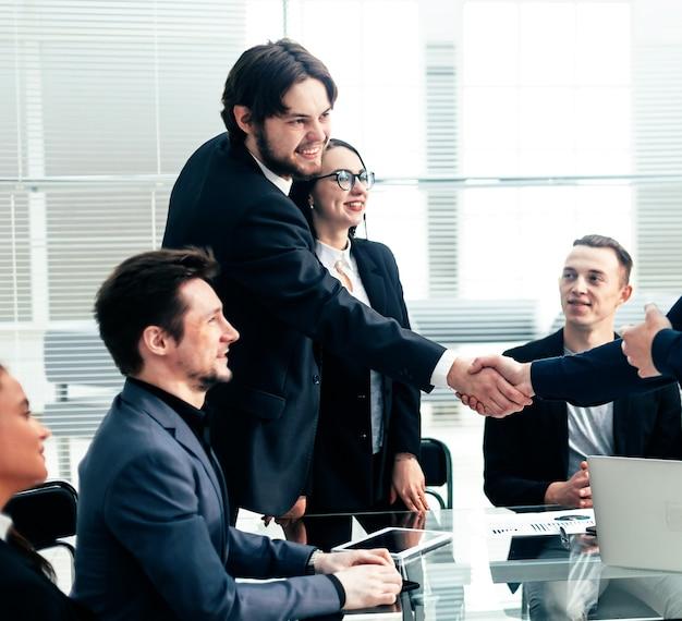사무실 책상 위에 악수 웃는 사업 사람들