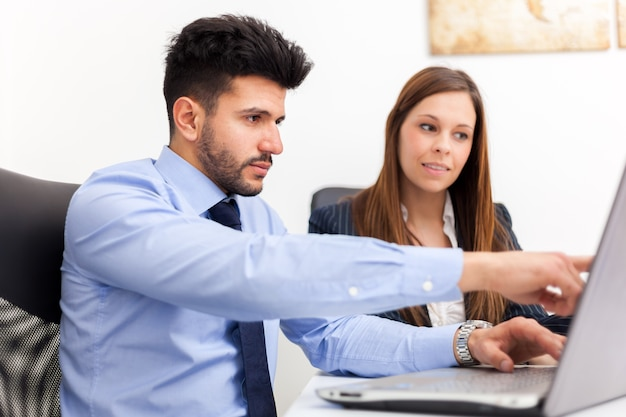Улыбаясь деловых людей, используя портативный компьютер в своем офисе