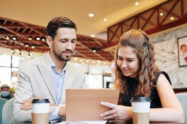 Улыбающиеся деловые люди смотрят презентацию нового продукта на планшетном компьютере
