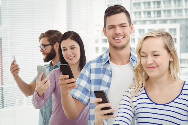 Smiling business professionals using smartphones while standing in row