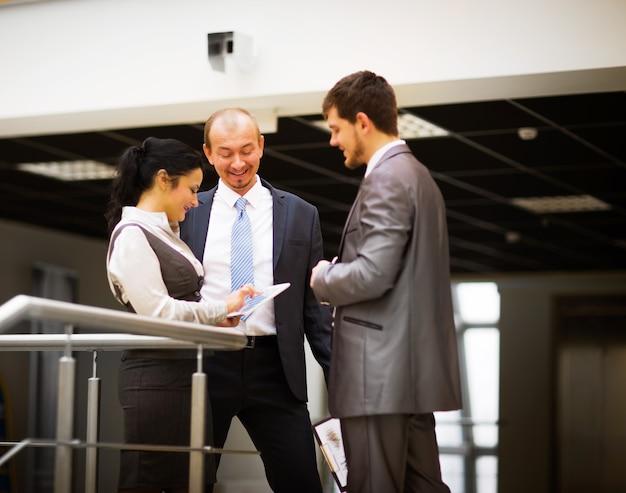 Улыбаясь бизнес-команда обсуждает что-то в офисе