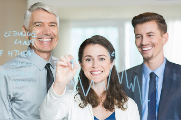 Smiling business team drawing graph on glass screen