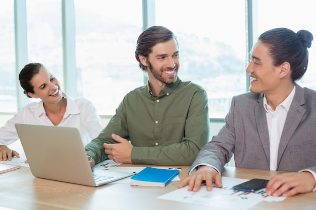 Smiling business team interacting with each other in conference room