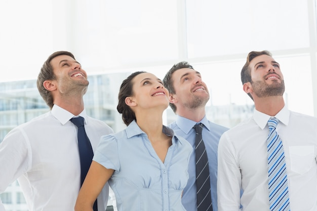 Smiling business team looking up