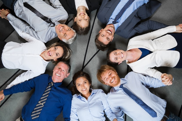 Smiling business team lying on floor in circle