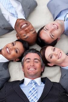 一緒に頭を持つ床に横たわる笑顔のビジネスチーム