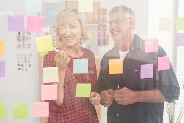 笑顔のビジネスチームは、壁にポストを指して