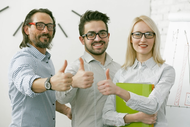 親指のジェスチャーを示す笑みを浮かべてビジネスチーム。男性と女性は、オフィスで一緒に立って成功の兆しを見せています。