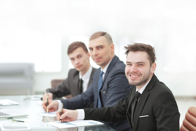 Улыбается бизнес-команда, сидя за столом в офисе.