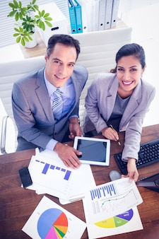 Smiling business team working in digital tablet