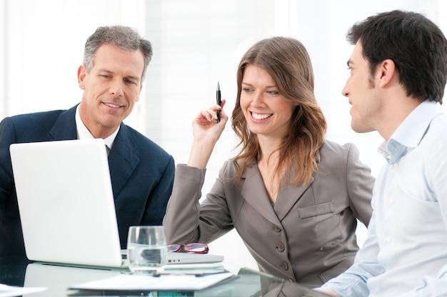 オフィスのラップトップコンピューターで一緒に働く笑顔の事業チーム