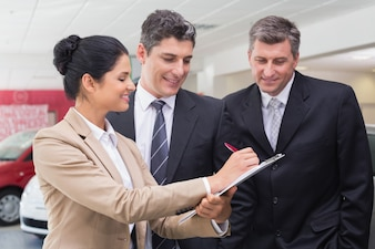 Smiling business team working together on clipboard at new car showroom