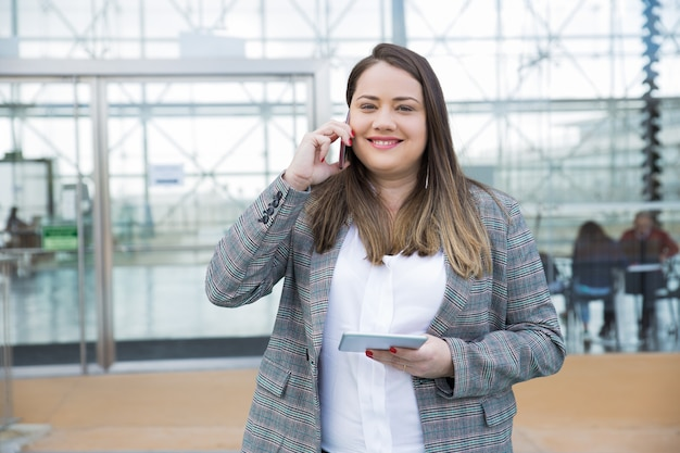 Smiling business woman calling on smartphone outdoors
