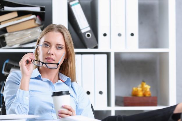 紙コップからコーヒーを飲んで笑顔のビジネス女性