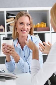 종이 컵에서 커피를 마시는 웃는 비즈니스 우먼