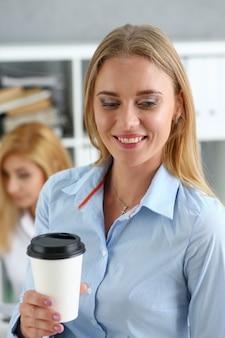 종이에서 커피를 마시는 웃는 비즈니스 우먼