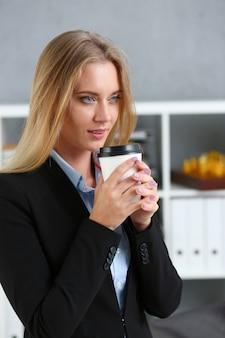 紙からコーヒーを飲んで笑顔のビジネス女性