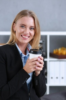 Smiling business woman drinking coffee from a paper cup in the office portrait looking directly