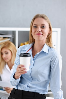 Smiling business woman drinking coffee from a paper cup
