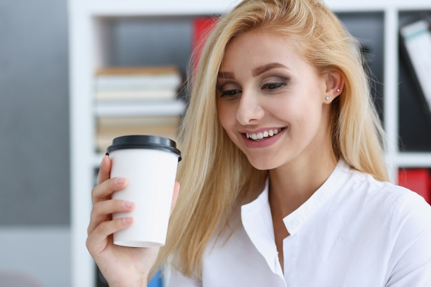 Smiling business woman drinking coffee from