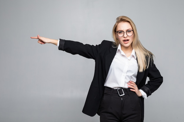 Smiling business woman finger pointing at the side isolated