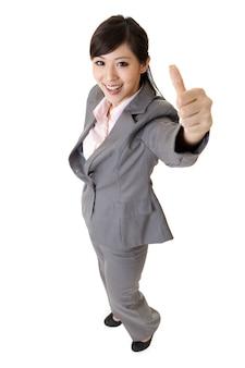 笑顔のビジネスウーマンはあなたに素晴らしい兆候を与えます