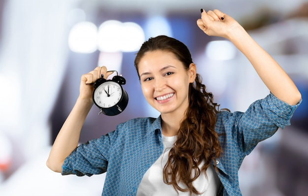Smiling business woman holding alarm clock. isolated portrait