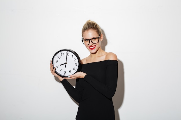 Smiling business woman holding clock.