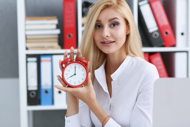 Smiling business woman holding in hand on the alarm clock a red color showing eight o'clock in the morning or evening am pm