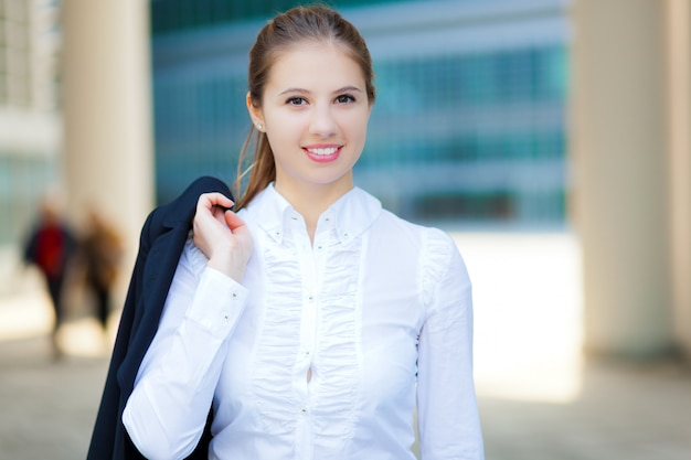Smiling business woman holding her jacket