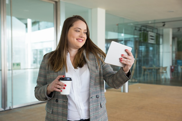 Smiling business woman holding tablet and drink outdoors