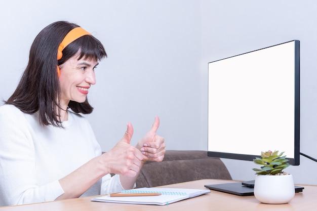 Улыбающаяся деловая женщина в наушниках смотрит в монитор с пустым белым экраном и держит палец вверх, показывая успех и согласие, вид сбоку, копировальное пространство
