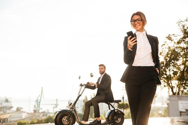 Улыбающиеся деловая женщина позирует на улице и с помощью телефона