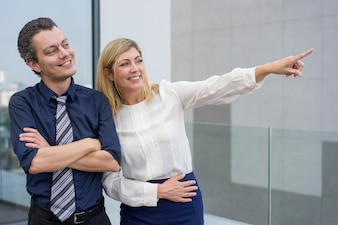 Smiling business woman showing male colleague something outdoors.