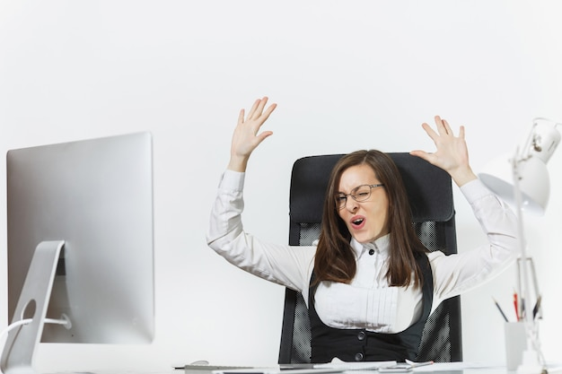 Smiling business woman sitting at the desk, working at computer with modern monitor and documents in office, rejoicing at success, holding hands up, copy space for advertisement