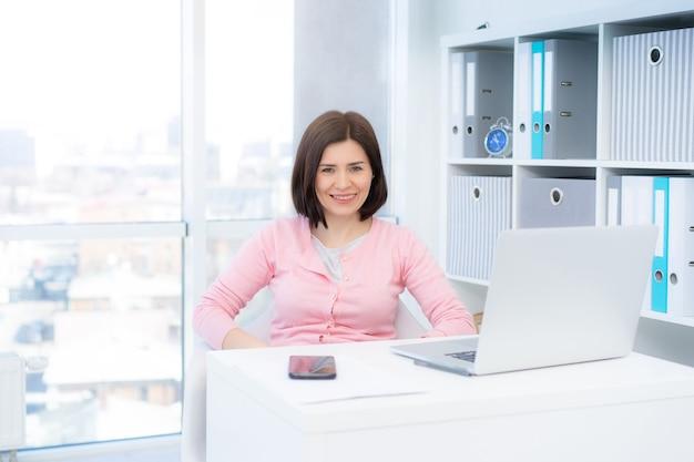 Улыбающаяся деловая женщина, сидящая в красивом офисе