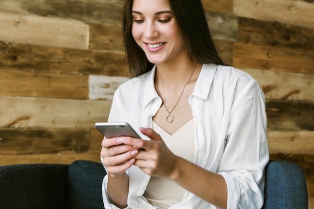ロフトスタイルで木製の壁の壁に青いアームチェアに座って笑顔のビジネス女性。