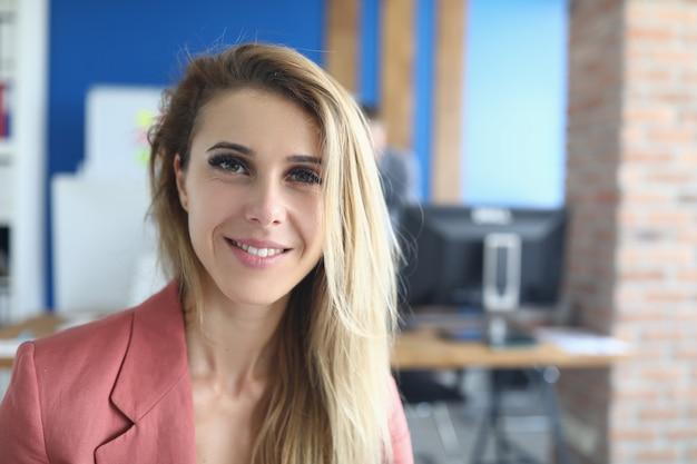 事務所に立っている笑顔のビジネス女性
