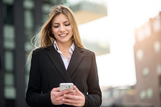 Smiling business woman using her mobile phone