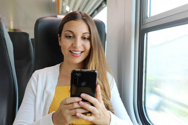 Smiling business woman using smartphone social media app while commuting to work in train.