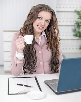 Улыбающаяся деловая женщина с чашкой кофе, сидя за вашим столом. бизнес фон