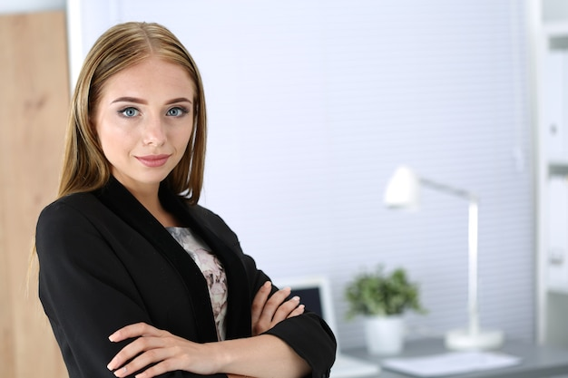 Улыбаясь бизнес-леди со сложенными руками, стоя в ее офисе. студент или молодой предприниматель