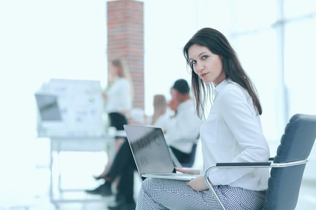 흐린 배경 사무실에 노트북으로 웃는 비즈니스 우먼.