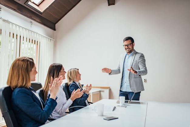 笑顔のリーダーに拍手を送るビジネス女性の笑みを浮かべてください。