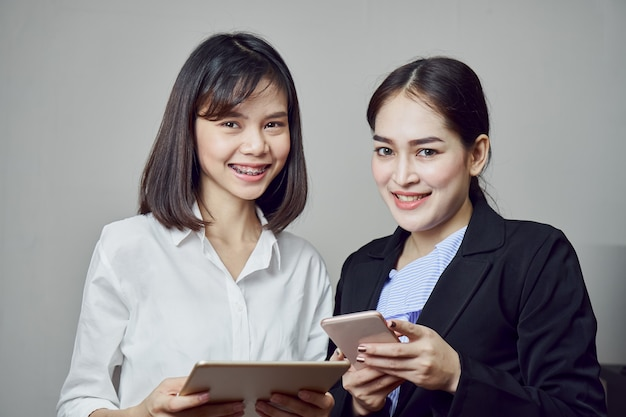 Smiling business women are holding tablet and using online applications.