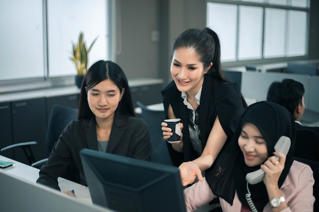 Улыбающаяся команда деловых женщин работает за офисным столом и обсуждает проект на компьютере