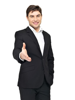 Smiling businessman in black suit gives handshake isolated on white.