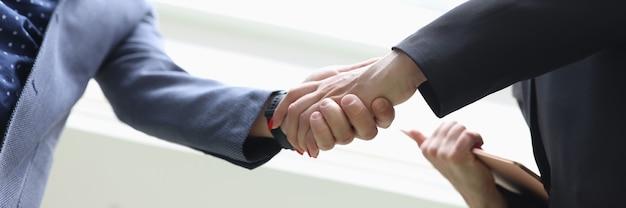 Smiling businessman and businesswoman shake hands closeup