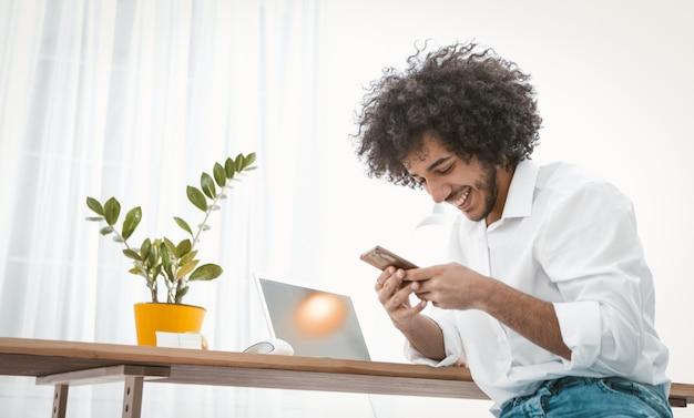 友達と携帯電話でチャット笑顔の実業家