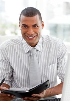 Smiling businessman consulting his agenda